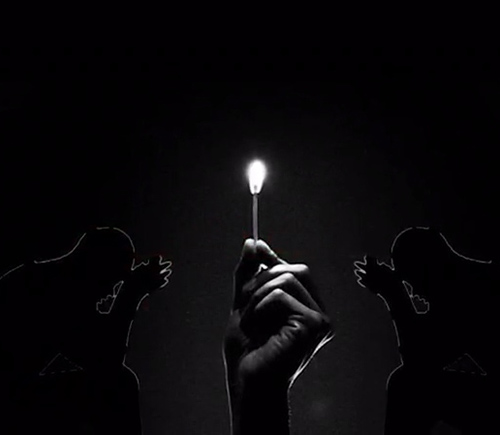 A hand holds a lit match in the center of the black and white image. flanked by the silhouettes of 2 men pray to Allah on either side